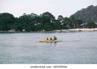Perhentian Island, Malaysia - 3 August 2017 : Family of father and son paddling kayak in Perhentian Island, Terengganu. The island is one of the most popular spot for tourists.