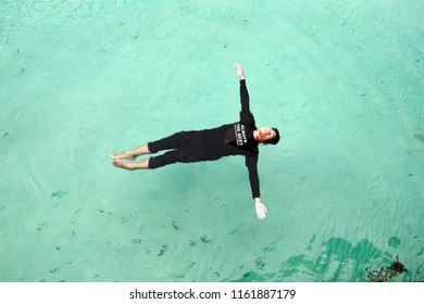 Perhentian  Island , Malaysia - August 15th, 2018 :Top view of sea diver  in a water suit is swimming with   fish