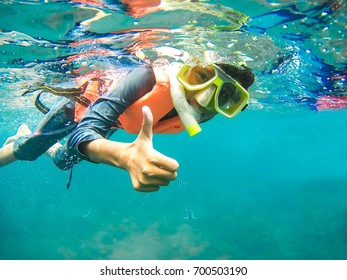 PERHENTIAN ISLAND,MALAYSIA-MARCH 23 2015:A Malay girl shows thumbs up during her snorkelling time
