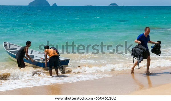 PERHENTIAN ISLANDS (Mira Beach), MALAYSIA - September 21, 2016: An unidentified tourist arrives to tropical island by taxi boat operated by two local men.