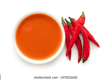 Peri peri chilli sauce in a white ceramic bowl next to a pile of red chillies isolated on white top view.