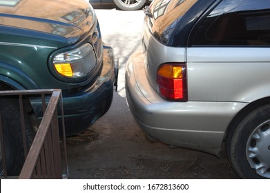 The perils of city street parking - a SUV parked inches from a car bumper. Both vehicles have scrapes, dings, cuts, scratches, damage, and dents caused by bad drivers that can't park