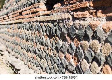 Perimeter wall of a house of ancient Rome with the layout of the brickwork that follows the technique of Opus Reticolatum