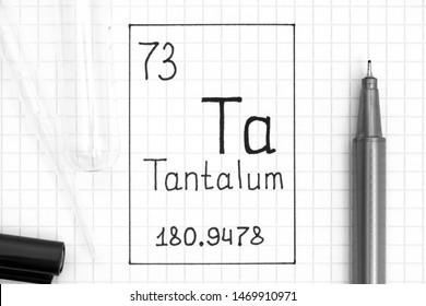 The Periodic table of elements. Handwriting chemical element Tantalum Ta with black pen, test tube and pipette. Close-up.