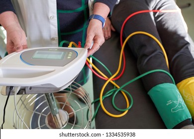 Peripheral artery disease measuring for patient ankle-brachial index (ABI) test limb ischemia. Medic hands working with device.