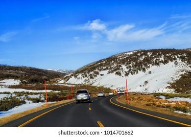 Perisher road high in SNowy mountains national park at winter during high skiing and snowboarding season. Toursts driving cars to the ski resort between snow covered hills and mountains.
