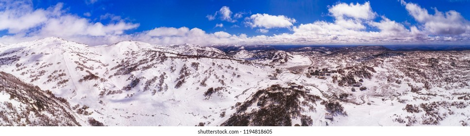 Perisher valley village between snow covered mountain ranges in Snowy mountains - popular australian winter sports resort for skiing and snowboarding.