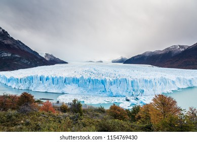 The Perito Moreno Glacier with cloudy sky and mountain with tree foreground, typical weather of Argentina, Patagonia