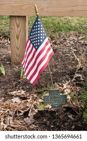 Perkasie, PA - April 7, 2019: Spanish American War Veteran memorial medallion holds an American flag at the Menlo Park Memorial garden.
