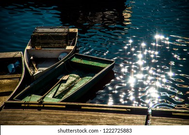 Perkins Cove, Maine, USA: October 21st, 2018: Three dory boats are tied together to a wooden dock on the left side of the frame with sunbursts reflecting off the ocean on the right side of the frame.
