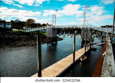 Perkins Cove, Ogunquit, Maine: October 20th, 2018: a wide shot of the Perkins Cove drawbridge with fishing boats in the background.