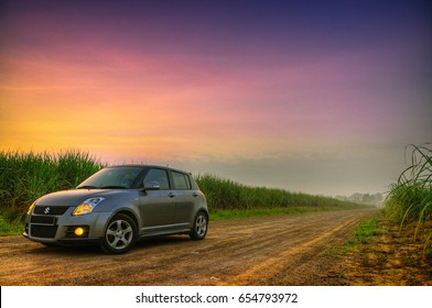 PERLIS, MALAYSIA - SEPTEMBER 1, 2011 : A grey Suzuki Swift in the middle of sugarcane farm in Perlis, Malaysia during sunrise