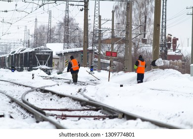 Perm, Russia - 17 February, 2019. Railwaymen clear the rails of snow at the Cable station