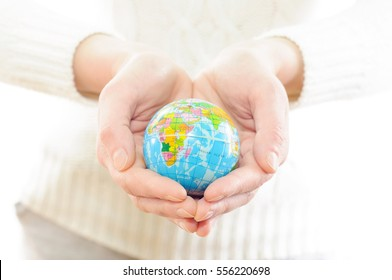 Perm, Russia - December 22, 2016 : Earth globe in hands. The concept of freedom, heart.