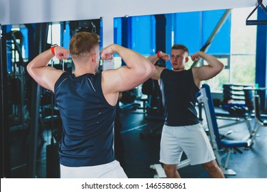 Perm, Russia - July 20, 2019: athlete in the gym looks in the mirror at his muscles, assessing the result of training