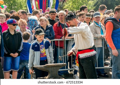 Perm, Russia - June, 12, 2017: Workshop on blacksmith's craft. The blacksmith's man shows the process of forging before a crowd of people.