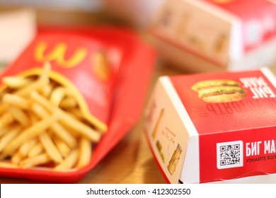 PERM, RUSSIA - MAY 15, 2015: (shallow dof) French fries, Big Mac in McDonalds restaurant. McDonalds Corporation - US corporation, large network of fast-food restaurants, working on franchise system