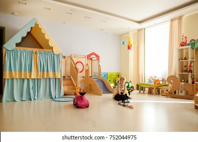 PERM, RUSSIA - may 18, 2015: Girl plays in the children's room or playroom. Beautiful interior and lots of toys. Blonde girl in a white dress. Kindergarten, game club, kids zone. General form