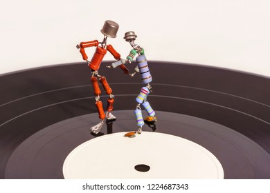 Perm, Russia - November 4, 2018: two funny small human figures, roughly welded together from resistors and transistors, dance on a vinyl record on a loght background