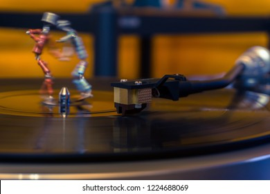 Perm, Russia - November 4, 2018: two funny small human figures, roughly welded together from resistors and transistors, dance on a rotating vinyl record in twilight; stylized as an vintage photo, focu