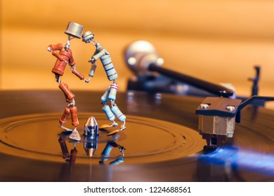 Perm, Russia - November 4, 2018: two funny small human figures, roughly welded together from resistors and transistors, dance on a rotating vinyl record in twilight; stylized as an vintage photo, slig