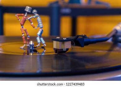 Perm, Russia - November 4, 2018: two funny small human figures, roughly welded together from resistors and transistors, dance on a rotating vinyl record in twilight; focus on phonograph stylus