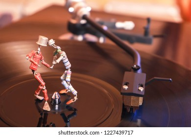 Perm, Russia - November 4, 2018: two funny small human figures, roughly welded together from resistors and transistors, dance on a rotating vinyl record in twilight; stylized as an vintage photo