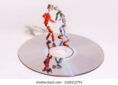 Perm, Russia - November 4, 2018: two funny small human figures, roughly welded together from resistors and transistors, dance on a compact disk on a light background