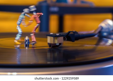 Perm, Russia - November 4, 2018: two funny small human figures, roughly welded together from resistors and transistors, dance on a rotating vinyl record in twilight; focus on phonograph tonearm