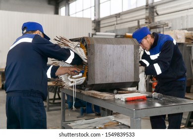 Perm, Russia - October 11, 2019: workers repairing a stator winding of an electric motor in a workshop