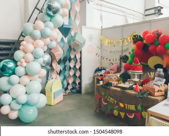 Perm, Russia/01.09.2019: Stand at the children's holiday fair. Photo zones of garlands of balloons and shiny piñatas. Beautiful tropical style table with fruit. Sale of holiday goods, party market.
