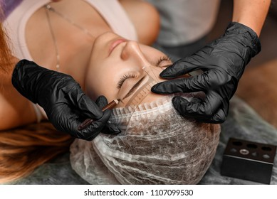 Permanent brow makeup in beauty salon, closeup. Professional beautician marks off the length of eyebrows with pencil and a special eyebrow measuring ruler. Cosmetology Treatment.