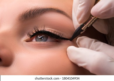 Permanent eye makeup close up shot. Cosmetologist applying tattooing of eyes. Makeup eyeliner procedure - Shutterstock ID 1804104934