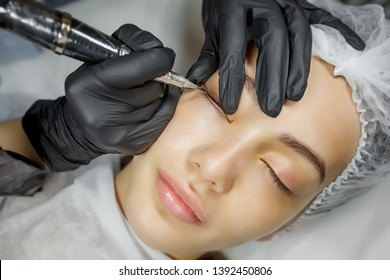Permanent make up eyeliner procedure, applying on young girl. Close-up. Young beautiful woman making permanent makeup in cosmetology salon. Young girl applying permanent eyeliner in beauty studio