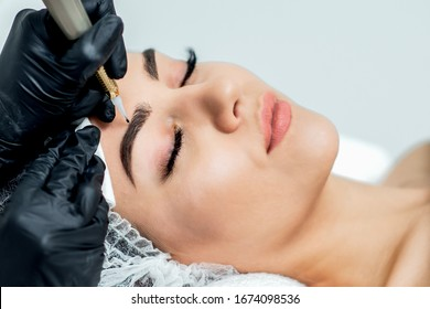 Permanent make up on eyebrows of young woman by professional cosmetologist close up.