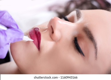 Permanent make up for red lips of beautiful woman in beauty salon. Beautician doing tattooing lips with red pigment. Close up, selective focus
