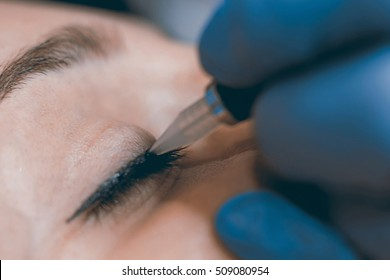 Permanent make up. Cosmetologist applying permanent makeup on eyes. Selective focus and shallow Depth of field