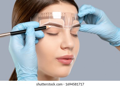 Permanent make-up for eyebrows of beautiful woman with thick brows in beauty salon. Closeup beautician doing tattooing eyebrow. Professional makeup and cosmetology skin care.