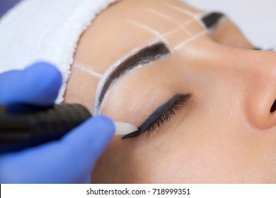 Permanent make-up for eyebrows of beautiful woman with thick brows in beauty salon. Closeup beautician doing  tattooing eyebrow.