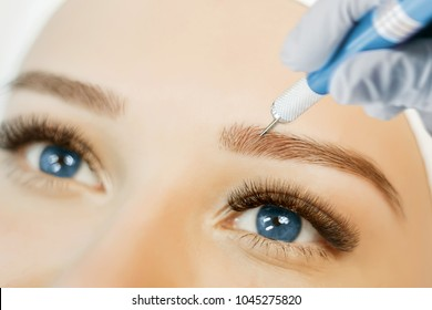 Permanent Makeup For Eyebrows. Microblading brow. Beautician Doing Eyebrow Tattooing For Female Face. Beautiful young girl in a beauty salon. Close up view of blue eyes with long eyelashes.