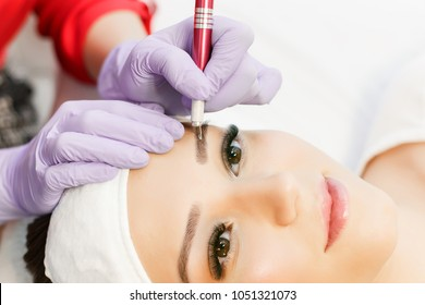 Permanent Makeup For Eyebrows. Microblading brow. Beautician Doing Eyebrow Tattooing For Female Face. Beautiful young girl in a beauty salon. Close up view of brown eyes with long eyelashes.