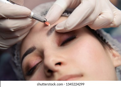 Permanent Makeup For Eyebrows. Microblading brow. Beautician Doing Eyebrow Tattooing For Female Face. Beautiful young girl in a beauty