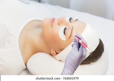 Permanent Makeup For Eyebrows. Microblading brow.  Beautician Doing Eyebrow Tattooing For Female Face. Beautiful young girl in a beauty salon.