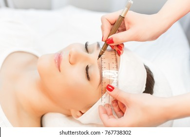 Permanent Makeup For Eyebrows. Microblading brow.  Beautician Doing Eyebrow Tattooing For Female Face. Beautiful young girl with long eyelashes tweezing her brows in a beauty salon.