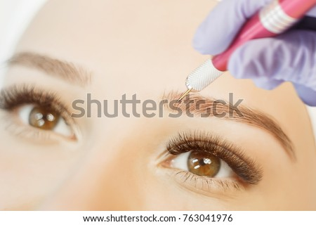 Permanent Makeup For Eyebrows. Microblading brow. Beautician Doing Eyebrow Tattooing For Female Face.