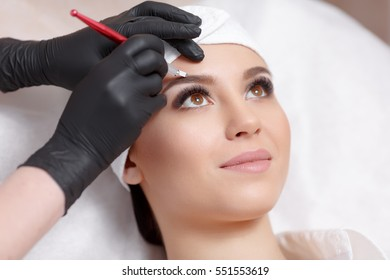 Permanent makeup eyebrows. Mikrobleyding eyebrows workflow in a beauty salon. Cosmetologist applying a special permanent makeup on a woman's eyebrows.