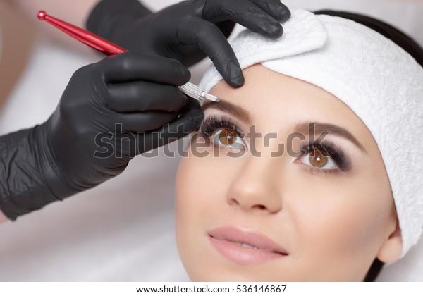 Dauerhafte Make-up-Augenbrauen. Mikrobleyding Augenbrauen Workflow in einem Schönheitssalon. Kosmetologe, die eine spezielle dauerhafte Schminke auf die Augenbrauen einer Frau auftragen.