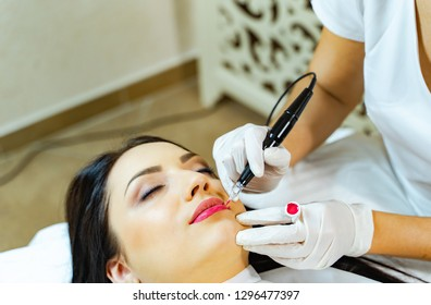 Permanent make-up for pink lips of beautiful woman in beauty salon. Beautician doing tattooing lips. Micropigmentation. Closeup