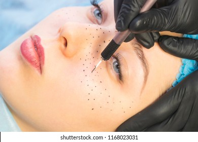 Permanent microblading tattooing freckles to a woman in a beauty salon