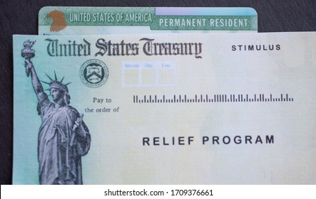 Permanent resident card of United States of America next to the Stimulus Check relief program. Benefits for green card holders concept.